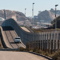 Border Patrol vehicle patrolling along the fence of the international border between San Diego, California and Tijuana, Mexico