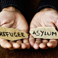hands hold out pieces of paper with words refugee and asylum