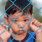 Little boy behind a fence left behind