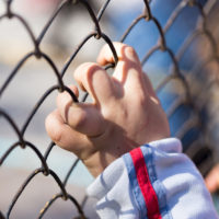 Immigrant child's hand on a grid of a metal fence