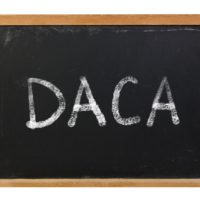DACA written on blackboard with white chalk