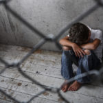 Depressed juvenile immigrant sitting alone behind a chain link fence