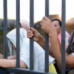 Refugee people holding metal bar at camp site