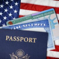 United States passport, social security card and resident card over american flag. Immigration concept